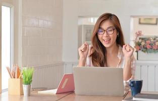 vrouwelijke tienerstudenten steken gelukkige handen op terwijl ze thuis online studeren met een laptop. foto
