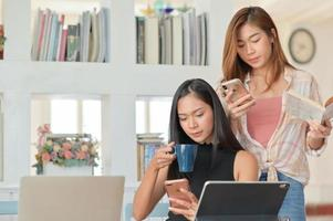 twee aziatische vrouwelijke studenten houden een koffiekopje vast en kijken naar een smartphone om zich voor te bereiden op graduate studies. foto
