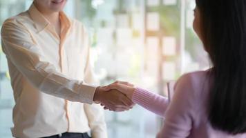 de nieuwe medewerkers schudden elkaar de hand om samen te werken in het moderne kantoor. foto