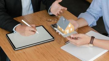 klanten luisteren naar aanbiedingen van thuismakelaars. met modelwoningen en tablet op tafel. foto