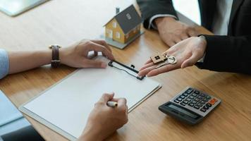 huismakelaar stelt de klant voor om het koopcontract te ondertekenen. foto