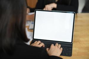 bijgesneden opname van een vrouwelijke werknemer die een toetsenbord typt op een laptop met een leeg wit scherm. foto