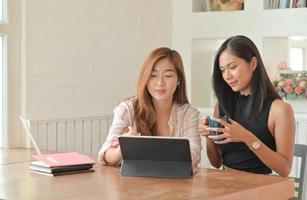 twee jonge vrouwelijke studenten met koffie gebruiken een laptop om in het zomersemester thuis online te studeren. foto