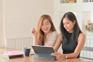 twee jonge vrouwelijke studenten die in het zomersemester een laptop gebruiken om thuis online te studeren. foto