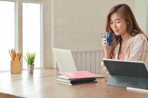 aziatisch studentenmeisje dat een koffiekopje vasthoudt en een laptop gebruikt, werkt aan een project om haar studie af te maken. foto