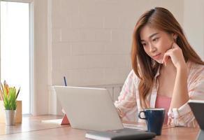 bijgesneden opname van vrouwelijke tienerstudent die thuis online studeert met een laptop. foto