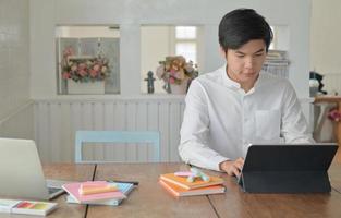 mannelijke studenten gebruiken laptop om thuis de zomer online te studeren. foto