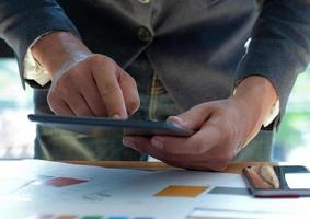 zakenmensen die aan een bureau werken en een tablet met touchscreen gebruiken. foto