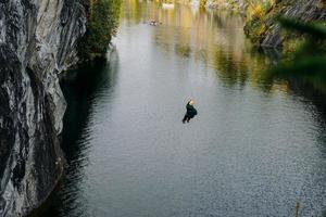 een man die uit een bungee springt over een kloof in het ruskeala-bergpark foto