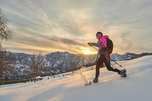 jonge sportieve vrouw bergafwaarts in de sneeuw met sneeuwschoenen in een zonsonderganglandschap foto