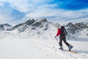 oudere man sportieve fit ski's bergop klimmen foto