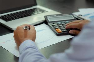 zakenman handen met pennen en zakelijke documenten aan bureau en rekenmachine. bedrijfs-, financiën-, belasting- en investeringsconcept. foto