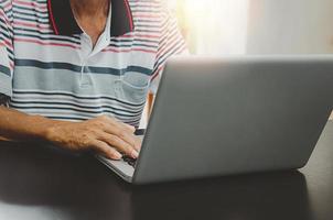 man hand met behulp van computer laptop op tafel thuis, zoeken naar informatie op internet surfen op het web, werken vanuit huis foto
