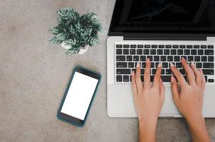 bovenaanzicht van een vrouwenhand met behulp van een laptopcomputertoetsenbord en een mobiele telefoon bespotten een leeg scherm. foto