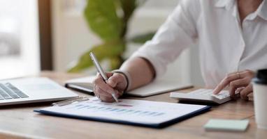 Aziatische zakenvrouw of accountant werken aanwijzende grafiek discussie en analyse data grafieken en grafieken en met behulp van een rekenmachine om getallen te berekenen. zakelijke financiën en boekhoudconcept foto