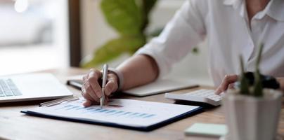 close-up van de hand zakenvrouw werkgegevens document grafiek grafiek verslag marketing onderzoek ontwikkeling planning beheer strategie analyse financiële en boekhoudkundige concept. foto