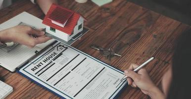 de makelaar legt de huisstijl uit aan de klanten die op bezoek komen om het huisontwerp en de koopovereenkomst, de goedkeuring van de hypothecaire lening woonkrediet en het verzekeringsconcept te bekijken. foto
