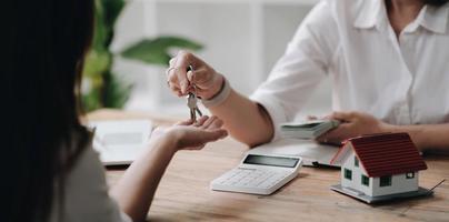 een nieuwe verhuurder krijgt een huissleutelketting van een makelaar na het betalen van een huisborg. makelaar en klant, investeringen in onroerend goed. foto