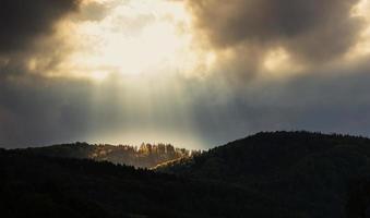 een gat in de lucht - de zon verlicht de top van de berg foto