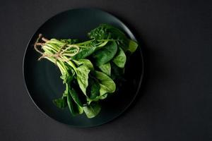 schoon voedselconcept. stelletje bladeren van verse biologische spinazie greens in een bord op een zwarte achtergrond. gezond detox lente-zomerdieet. veganistisch rauw voedsel. ruimte kopiëren. foto