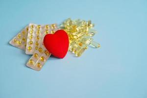 omega 3 capsules met rood hart. visolie in tabletten. gezondheidsondersteuning en hartbehandeling. het medicijn. foto