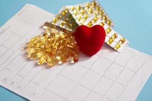 omega-3 capsules liggen op een cardiogram naast een rood hart. visolie in tabletten. gezondheidsondersteuning en hartbehandeling. foto