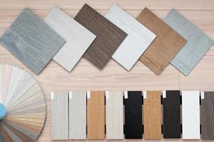 een voorbeeld van een catalogus van luxe vinyl vloertegels en een designpalet met texturen met een nieuw interieurontwerp voor een huis of vloer op een lichte houten achtergrond. foto