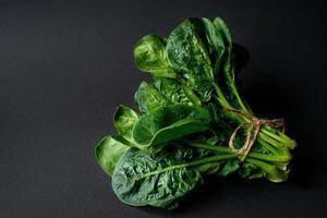 schoon voedselconcept. stelletje bladeren van verse biologische spinazie greens op een zwarte achtergrond. gezond detox lente-zomerdieet. veganistisch rauw voedsel. foto