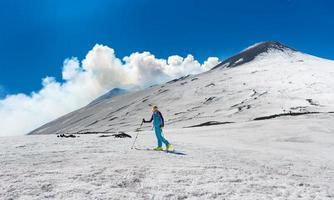 meisje skitochten onder de top van de krater van de berg etna foto