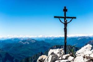 klein ijzeren kruisbeeld bovenop een berg foto