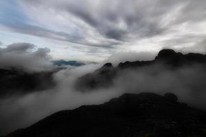 berglandschap in de avond met het spel van wolken tussen de toppen foto