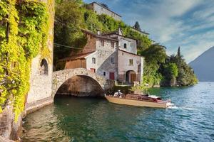 ouderwetse toeristische houten speedboot die een oude stenen brug nadert aan het comomeer foto