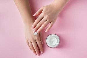 vrouwelijke handen met een fles crème op roze achtergrond. spa- en lichaamsverzorgingsconcept. afbeelding voor reclame. foto