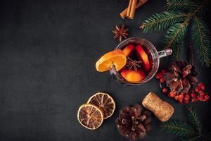 traditionele kerstverwarmende glühwein. warme drank met kruiden in glazen beker op donkere achtergrond. foto