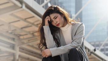 ontslaan. ontslagen. ontslagen zakenvrouw zittend op trappen van kantoorgebouw buiten. foto
