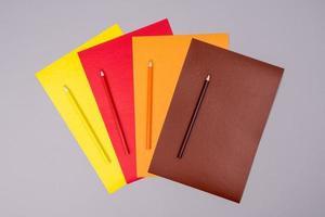gele, rode, oranje en bruine potloden met gekleurd papier op een grijze achtergrond foto