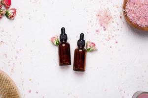 natuurlijke olieflessen met bloemen en badzout op witte achtergrond foto