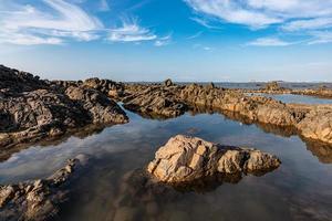 het zeewater tussen de kustriffen weerspiegelt de gele riffen en de blauwe lucht foto