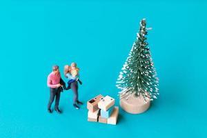 miniatuurmensen, gelukkige familie die naast een kerstboom staat foto