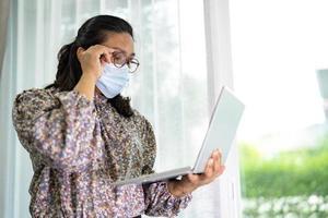 aziatische dame zakenvrouw werk vanuit huis communiceren naar kantoor via een videoconferentiegesprek op laptop, thuis blijven. foto