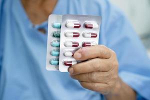 Aziatische senior vrouw patiënt met antibiotica capsule pillen in blisterverpakking voor behandeling infectie patiënt in ziekenhuis, apotheek drogisterij concept. apotheek drogisterij concept. foto