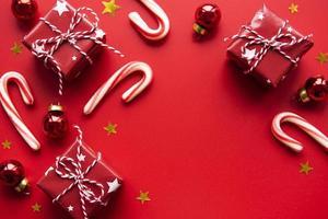 rode kerstballen, geschenkdozen en snoeprietdecoratie op rode achtergrond met kopieerruimte foto