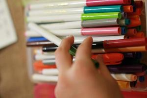 close-up shot van een hand die een marker van een stapel grijpt foto