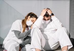 vermoeide medici slapen samen op de vloer op het terras van de kliniek foto