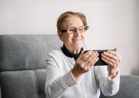 lachende senior vrouw met videogesprek op smartphone foto