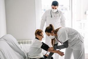 artsen die de bloeddruk van een oudere vrouw diagnosticeren foto