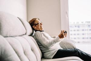 tevreden oudere vrouw met console die videogame speelt foto