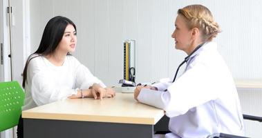 arts die medicatie ontmoet en uitlegt aan vrouwelijke patiënt in zijn kantoor in ziekenhuizen foto