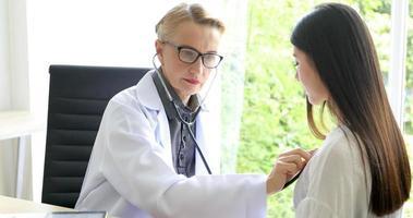 arts die een stethoscoop gebruikt voor het onderzoeken van de patiënt in zijn kantoor in ziekenhuizen foto