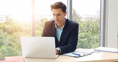 zakenlieden die een notebook gebruiken en serieus zijn over het verrichte werk tot de hoofdpijn foto
